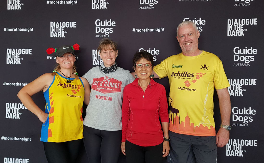 Four Achilles guides stand arm in arm in front of a black Dialogue in the Dark and Guide Dogs Australia banner