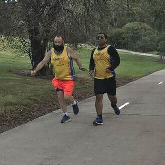 Paul, left, wearing Achilles singlet and orange shorts guides Amir via a hand-hand tether. Amir wears an Achilles singlet and black shorts. They are running on a concrete path with a weeping winter tree behind them