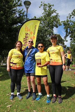 Left to right: 2nd place Brooke, 3rd place Kevin, 1st place Will (holding plaque) and organiser Adrienne. Achilles flag and trees in background